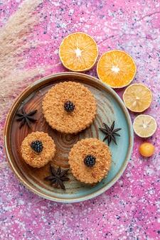 Вид сверху маленьких вкусных пирожных с дольками апельсина на розовой поверхности