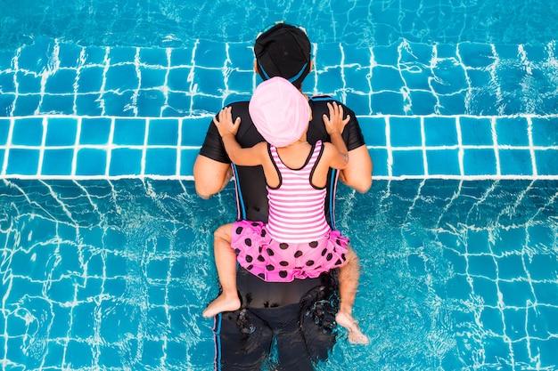 Вид сверху маленькая девочка, плавающая с матерью в бассейне