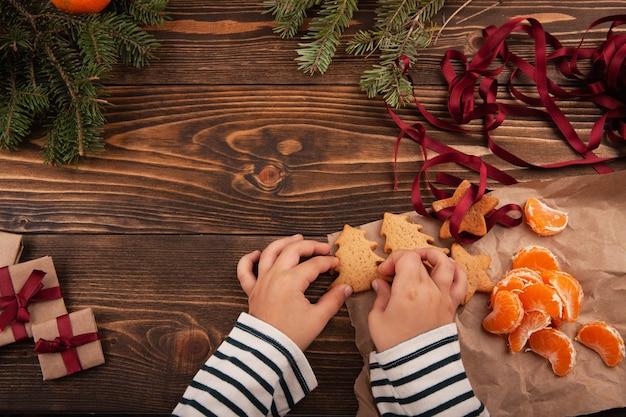 테이블에 좌석과 그의 손에 크리스마스 쿠키를 들고 작은 아이의 상위 뷰.