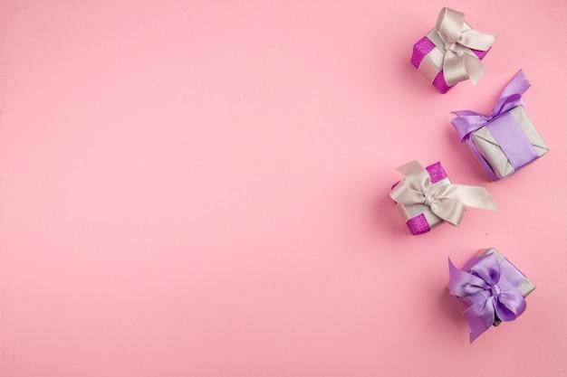 Вид сверху маленьких подарков на розовой поверхности