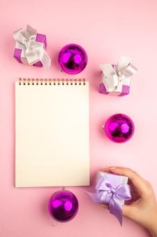 Вид сверху маленьких подарков с елочными игрушками и блокнотом на розовой поверхности