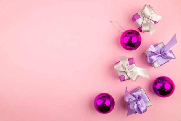 ピンクの表面にクリスマスツリーのおもちゃと小さなプレゼントの上面図