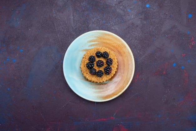 暗い表面のプレートの内側にベリーと小さな丸いケーキの上面図