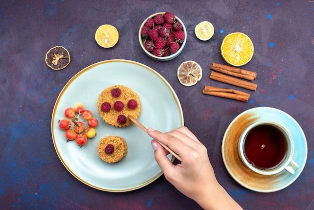 暗い表面にフルーツシナモンティーとプレートの内側に新鮮なラズベリーと小さな丸いケーキの上面図