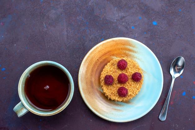 Вид сверху маленького круглого торта со свежей малиной внутри тарелки с чаем на темно-синей поверхности