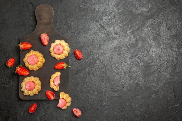 灰色の表面にイチゴクリームと小さなシュガークッキーの上面図
