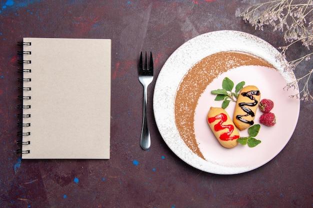 블랙에 디자인 된 접시 안에 작은 달콤한 비스킷의 상위 뷰