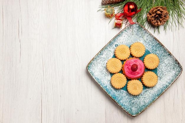 白いテーブルの上のプレートの内側にフルーツケーキと小さな甘いクッキーの上面図
