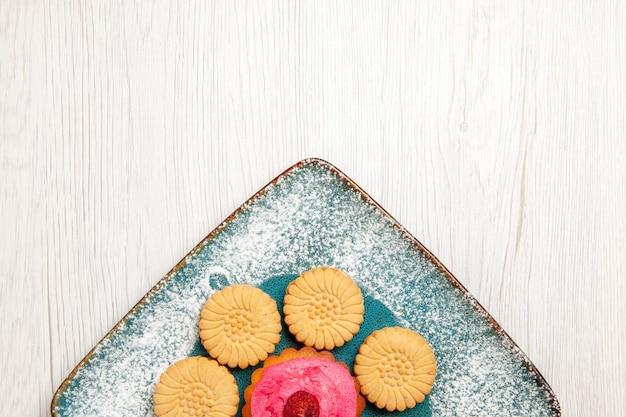 흰색 테이블에 접시 안에 과일 케이크와 함께 작은 달콤한 쿠키의 상위 뷰