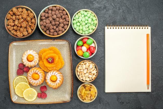 灰色のレモンスライスみかんとキャンディーと小さなおいしいケーキの上面図