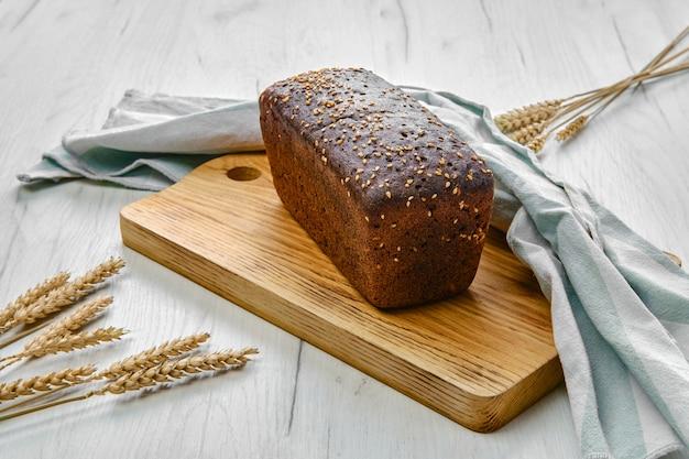 Вид сверху буханки черного хлеба на закваске с семечками и кунжутом