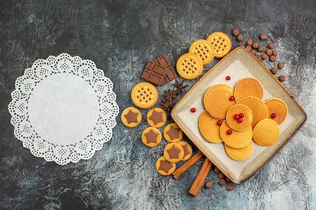 많은 맛있는 과자와 회색 배경에 흰색 레이스 조각의 상위 뷰