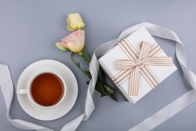 Вид сверху прекрасных цветов с белой лентой подарочной коробки и чашкой чая на сером фоне