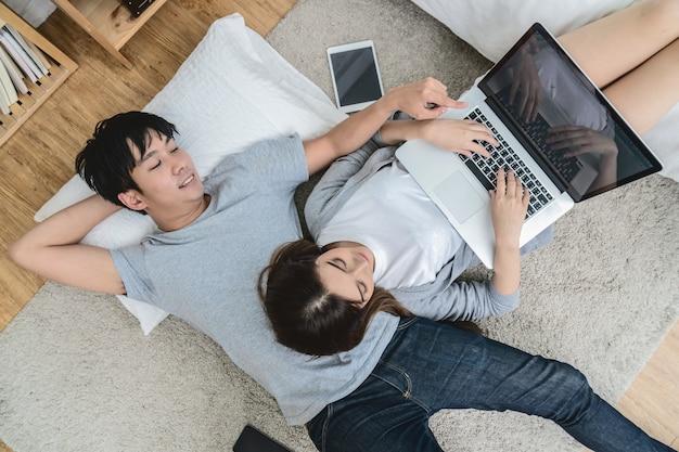 カーペットの床に眠っている近代家庭でデジタルタブレットを使用している恋人のトップビュー