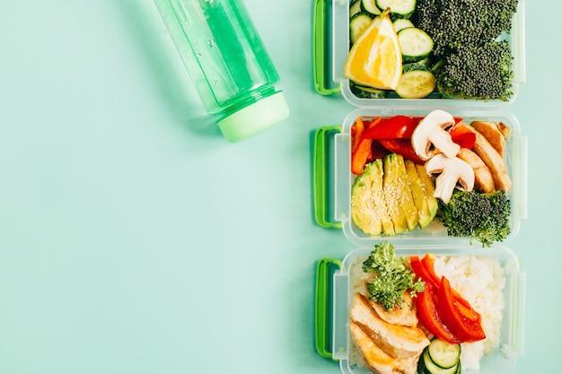 Вид сверху на ланч-боксы с едой, рисом, мясом, овощами и фруктами на зеленом фоне со свободным пространством для текста