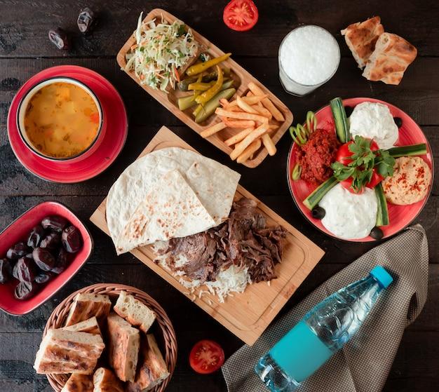 Вид сверху на обед с супом, шашлыком и рисом и гарнирами