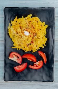 木製の表面にマカロニパスタと皿にスライスしたトマトのトップビュー