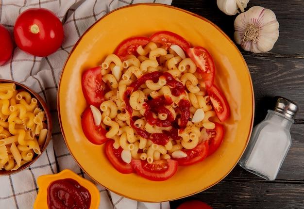 Вид сверху макароны макароны в тарелку с помидорами