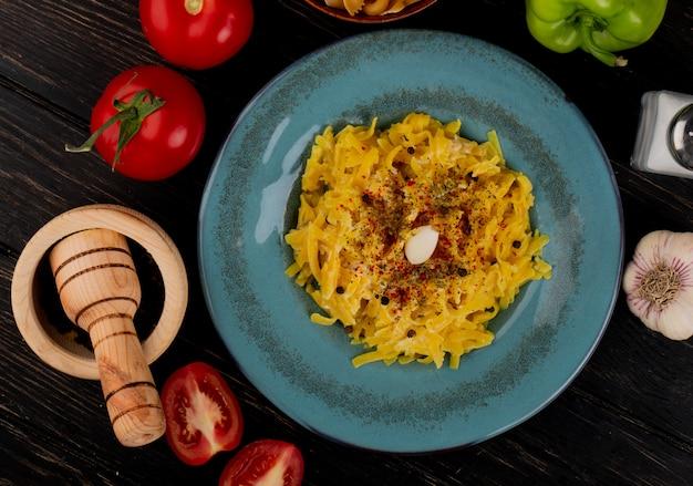 Вид сверху макаронных макарон в тарелке с целыми и нарезанными помидорами