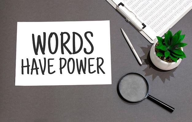 Words have powerサインで書かれた虫眼鏡、電卓、ペン、植物、ノートの上面図