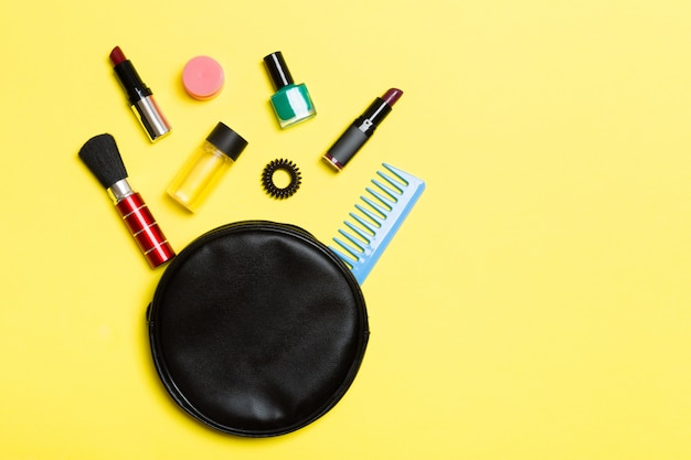 Взгляд сверху составляет продукты упаденные из косметики кладут в мешки на желтом цвете.