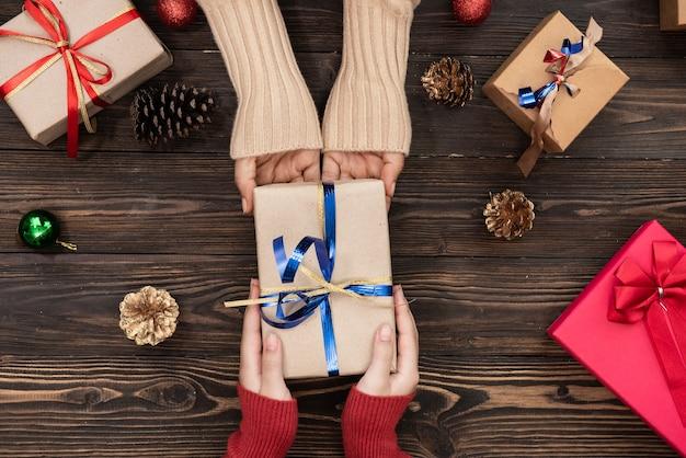 ピンクの背景に赤いギフト ボックスを保持している男性と女性の手の平面図が横たわっていた。誕生日、バレンタインデー、クリスマス、新年のプレゼント。おめでとう背景コピー スペース。