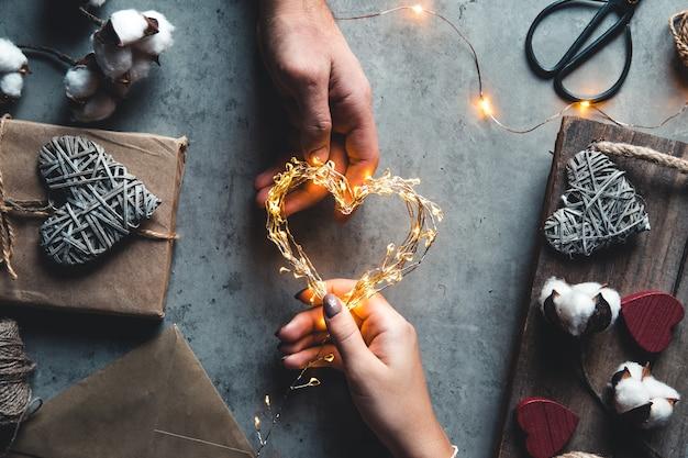 Вид сверху на мужские и женские руки, держащие красную подарочную коробку с золотой лентой