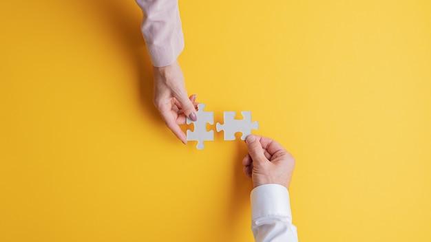 概念的なイメージで一緒に2つの一致するパズルのピースを結合する男性と女性の手の上面図。黄色の背景の上。