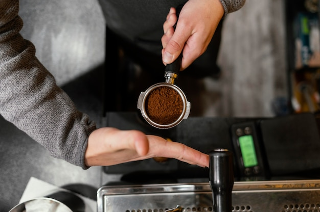 プロのコーヒーマシンカップを保持している男性のバリスタの上面図