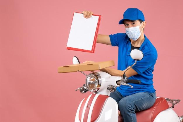 복숭아 배경에 문서를 들고 주문을 전달하는 스쿠터에 앉아 모자를 쓰고 마스크에 남성 배달 사람의 상위 뷰