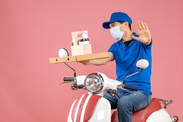 パステル調の桃の背景に5つの注文を示すスクーターに座っている帽子をかぶったマスクの男性配達員のトップビュー