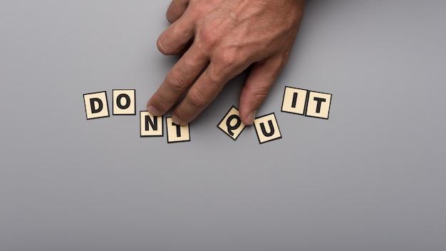 灰色の背景の上に紙カット文字でそれを行うサインを作成する男性の手の上面図。
