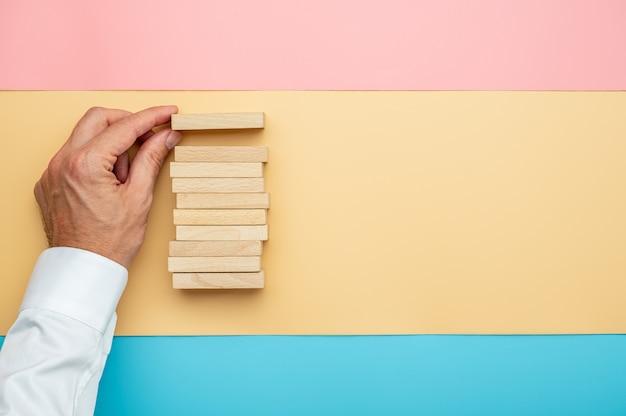 Взгляд сверху мужской руки делая стог деревянных блоков