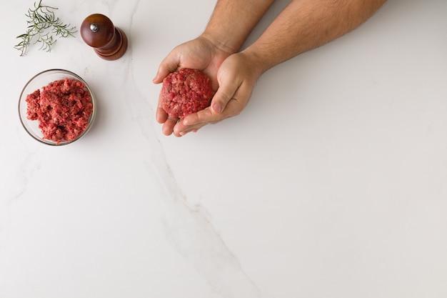 大理石のテーブルでハンバーガーを成形する男性の手の平面図、肉のガラスのボウル、コショウグラインダー、ローズマリーテキスト用のスペース