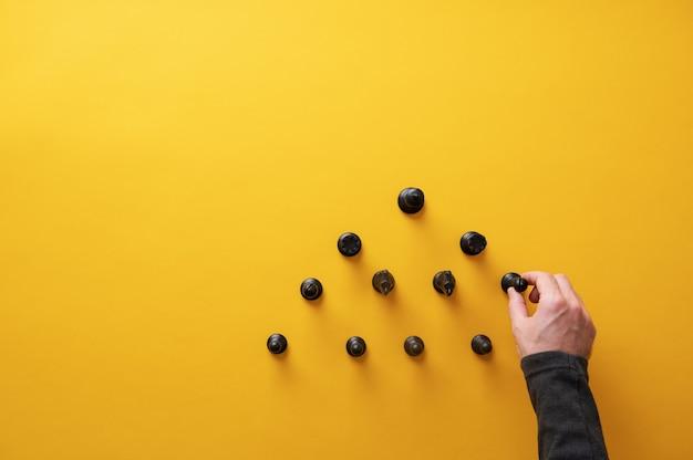 概念的なイメージのピラミッド構造でチェスの駒を配置する男性の手の上面図。コピースペースのある黄色の背景の上