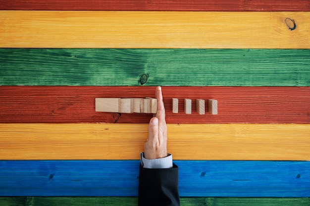 カラフルな木製の背景の上のドミノ効果を停止する男性の手の上面図。