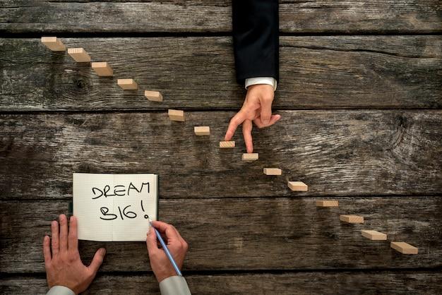 Вид сверху мужской руки, пишущей обнадеживающее сообщение мечтайте о большом в блокноте, пока бизнесмен поднимает пальцы вверх по деревянным колышкам, напоминающим лестницу.