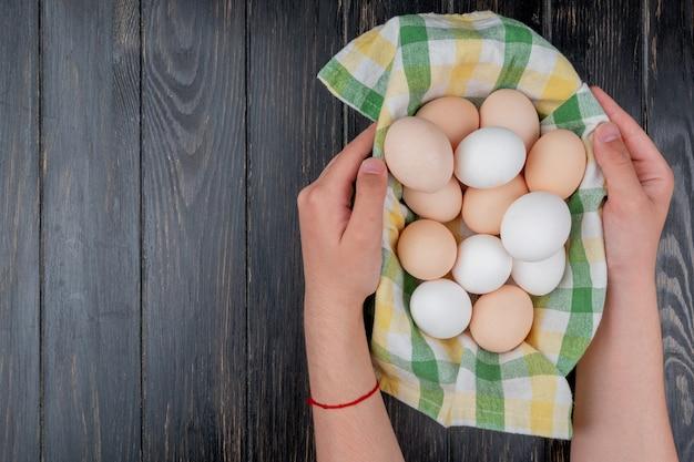 Вид сверху на мужские руки, держащие несколько свежих куриных яиц на проверенной скатерти на деревянном фоне