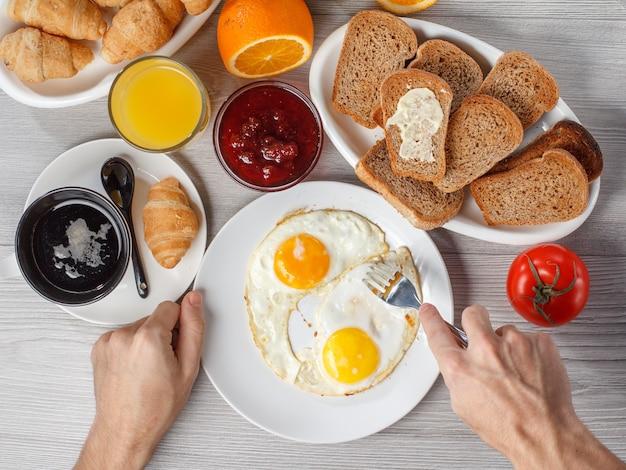 블랙 커피, 크루아상, 딸기 잼이 든 그릇, 접시에 빵, 신선한 오렌지 주스와 함께 테이블에 튀긴 계란과 포크가 있는 접시를 들고 있는 남성 손의 상위 뷰