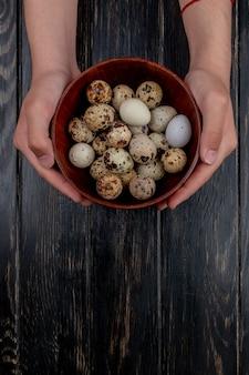 Вид сверху на мужские руки, держащие перепелиные яйца на деревянной миске на деревянном фоне с копией пространства