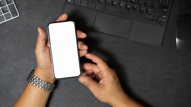 スマートフォンを持っている男性の手の上面図は彼の机のモバイルアプリケーション画面のモックアップに座っています