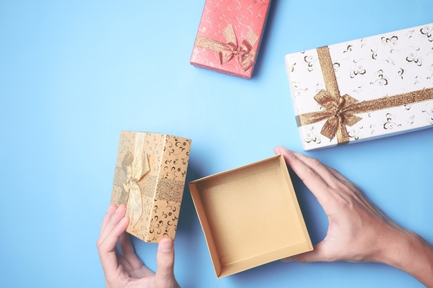 선물 상자를 여는 남성 손의 상위 뷰는 파란색 배경에 표시합니다.