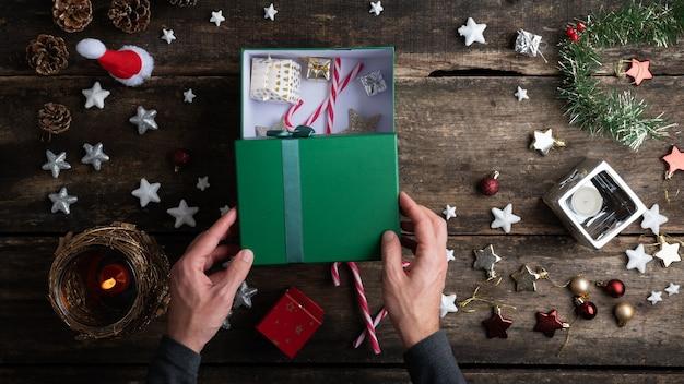 緑のホリデーギフトボックスを開く男性の手の上面図