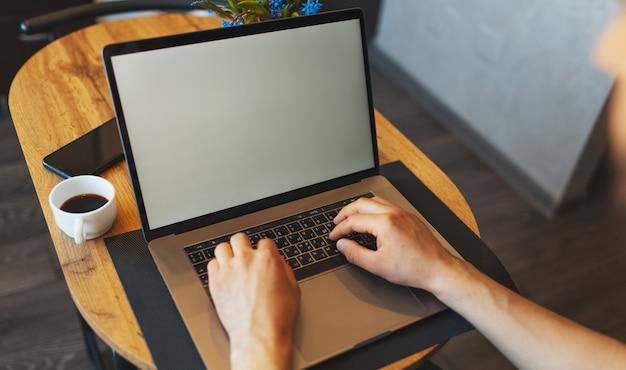 Вид сверху мужских рук, набрав на клавиатуре компьютера человек, работающий на смартфоне ноутбука и кофейной чашке на деревянном столе.