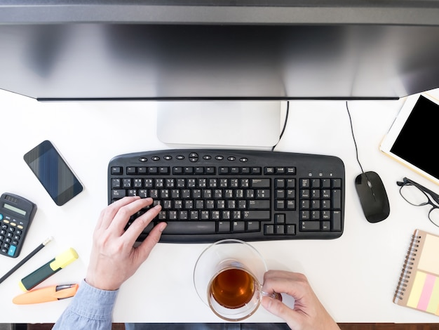컴퓨터에서 작업 하 고 책상에 차 컵을 들고 남성 손의 최고 볼 수 있습니다.