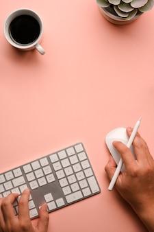 クリエイティブなワークスペースでコンピューターのマウスとキーボードを操作する男性の手の上面図