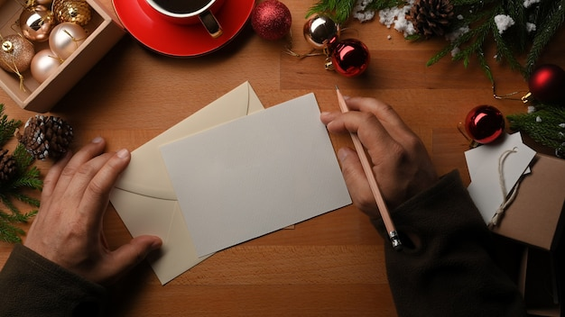 크리스마스 장식으로 장식 된 나무 테이블에 인사말 카드를 쓰는 남성 손의 상위 뷰