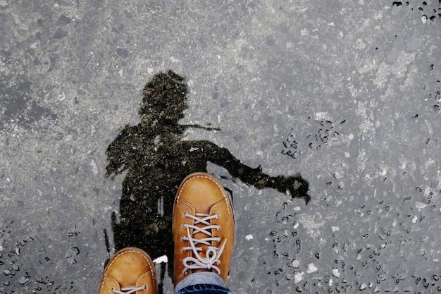 雨が降った後の濡れた地面を歩く男性のトップビュー