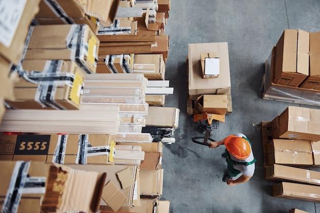 Вид сверху мужского работника на складе с тележкой для поддонов.
