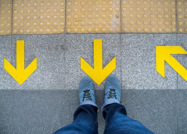 Взгляд сверху ног человека стоя над символом стрелки на платформе метро.